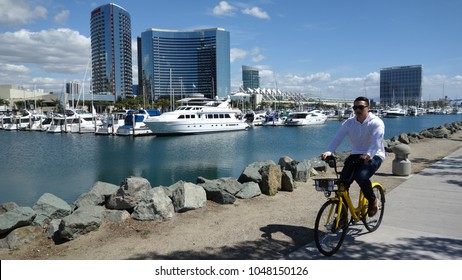 San Diego, CA / USA - March 16, 2018: A man rides a Ofo rental bike along the San Diego marina in Embarcadero Marina Park, as city embraces dockles bike sharing