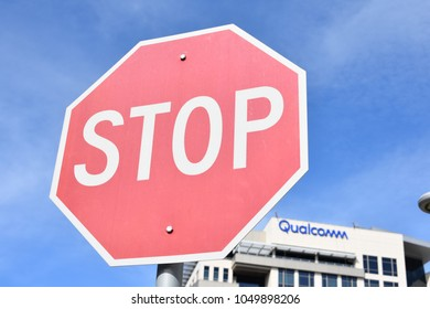San Diego, CA / USA - March 16, 2018 : US government says NO to Qualcomm- Broadcomm deal. Picture showing Stop sign with Qualcomm (new logo)  building in the background.