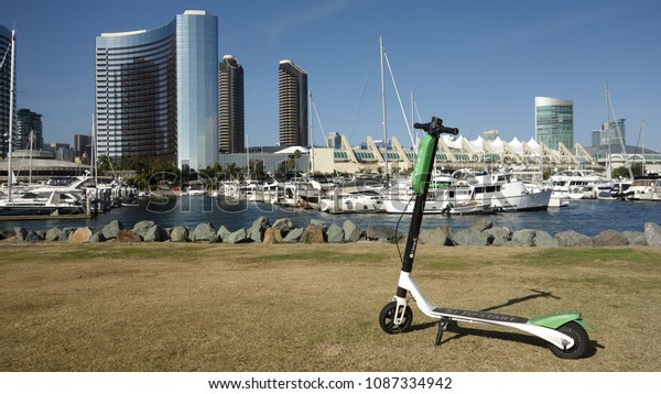 San Diego, CA / USA - May 7, 2018: A green Limebike Lime-S electric scooter is parked in San Diego's Embarcadero Marina Park, overlooking the marina and partial skyline on a sunny day