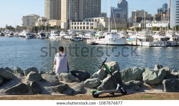 San Diego, CA / USA - May 8, 2018: A young man relaxes by the waterfront and enjoys the view of the skyline after riding a Limebike Lime-S electric scooter around Embarcadero Marina Park