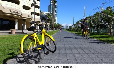 San Diego, CA / USA - September 16, 2018: A yellow OFO dockless bike is parked in downtown as a man bicycles by