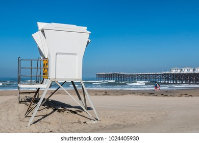 SAN DIEGO, CALIFORNIA - APRIL 21, 2017:  People enjoy Pacific Beach between a lifeguard tower and Crystal Pier, a fishing pier with rental cottages lining the top.