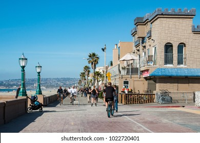 SAN DIEGO, CALIFORNIA - FEBRUARY 9, 2018:  People ride bikes on the Mission Beach boardwalk, a concrete walkway shared by walkers and bicyclists spanning 3-1/2 miles in total length.