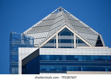 San Diego, California. March 1, 2018. Background texture of a modern architecture skyscraper facade with symmetrical blue glass windows and a white panel metal rooftop against a blue sky.