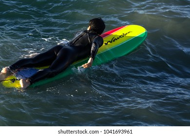 SAN DIEGO, CALIFORNIA - NOVEMBER 9, 2017: An unidentified surfer on a colorful surfboard waits for a wave near the Pacific Beach Pier.