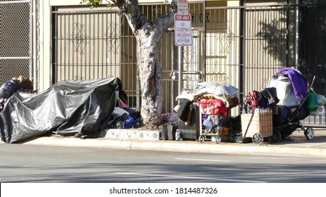 SAN DIEGO, CALIFORNIA USA - 4 JAN 2020: Stuff of homeless street people on walkway, truck on roadside. Begging problem in downtown of city near Los Angeles. Jobless beggars live on pavements.