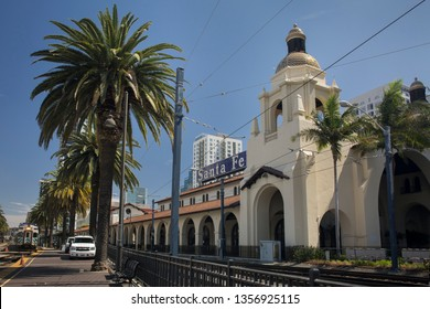 San Diego, California, USA – July 27, 2017: Horizontal view of Santa Fe Depot Victorian-style façade by the train tracks and palm trees