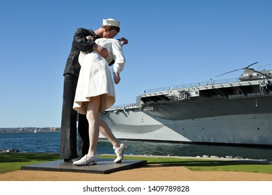 """SAN DIEGO, CALIFORNIA / USA - NOVEMBER 29 2009: Iconic """"Unconditional Surrender Statue"""" with American sailor kissing nurse in white uniform at Tuna Harbor Park on San Diego Bay."""