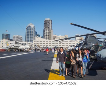 SAN DIEGO, CALIFORNIA / USA - October 19, 2013: A group of Asian visitors observing different models of aircrafts at Midway Aircraft Carrier.