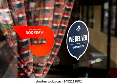 San Diego, California/United States - 05/31/2019: Several restaurant window stickers advertising delivery available through DoorDash and Postmates