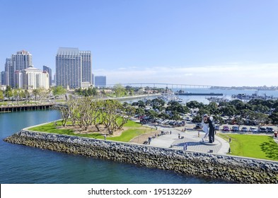 SAN DIEGO, USA - FEBRUARY 24 2014: The sculpture of unconditional surrender, of a sailor kissing a nurse after the end of world war II, the San Diego skyline and the Coronado bridge in the background.