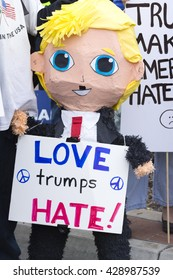 """SAN DIEGO, USA - MAY 27, 2016: A Mexican pinata in the form of a smiling Donald Trump holds a sign reading """"Love trumps hate"""" at a protest outside a Trump rally in San Diego."""
