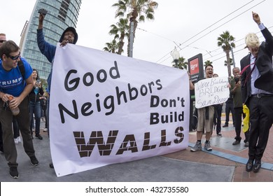 SAN DIEGO, USA - MAY 27, 2016: Anti-Trump protesters display their opinion about the wall while a Trump fan smiles at their efforts during a protest outside a Trump rally in San Diego.
