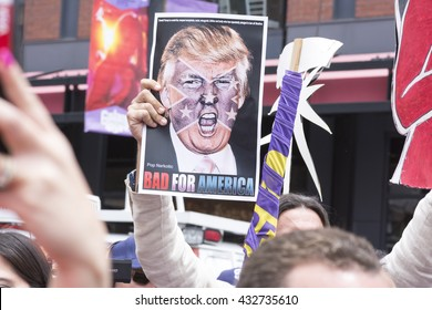 "SAN DIEGO, USA - MAY 27, 2016: A protester holds a sign featuring an angry photo of Donald Trump and reading ""Bad for America"" at an anti-Trump protest outside a Trump rally in San Diego."