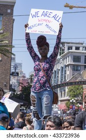 "SAN DIEGO, USA - MAY 27, 2016: An Afro American woman holds high a sign reading ""We are all women"" at an anti-Trump protest outside a Trump rally in San Diego."