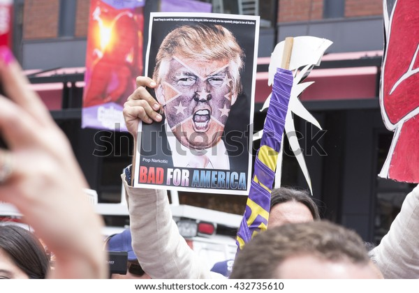 """SAN DIEGO, USA - MAY 27, 2016: A protester holds a sign featuring an angry photo of Donald Trump and reading """"Bad for America"""" at an anti-Trump protest outside a Trump rally in San Diego."""