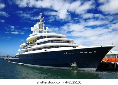 SAN DIEGO/CALIFORNIA, UNITED STATES - CIRCA FEBRUARY, 2013: Large luxury ocean motor yacht LUNA moored to boat pier with yacht structure reflecting on water against blue sky detail landscape wide view