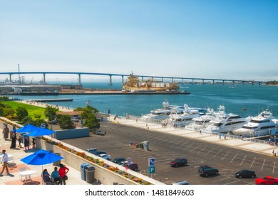 San Diego/USA - August 11, 2019. San Diego Marina Harbor. Luxury Yachts in Embarcadero Park South, Coronado Bridge, and People Enjoying Sunny Day's Promenade. View from San Diego Convention Center.