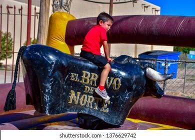 San Elizario, Texas / USA - 21 April 2019 Little boy riding a mechanical bull.