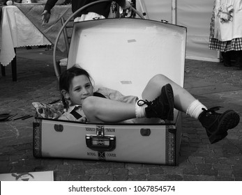 San Felice sul Panaro, Italy - Magico 2018, Magic Carnival. The theme of this year was the silent movie. A little girl lying down in a suitcase, She is playing. Black and white photo.