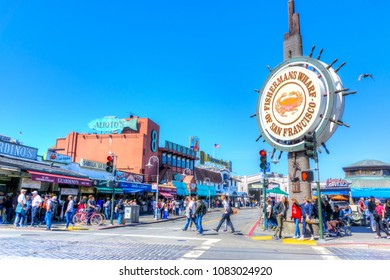 SAN FRANCISCO - APR 2, 2018: A crowd visiting the Fisherman's Wharf. The popular waterfront district is famous for its many attractions, souvenir shops and stalls selling crab and clam chowder.
