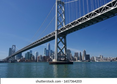 San Francisco Bay bridge frames downtown San Francisco underneath. Saleforce tower is featured within the frame