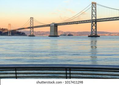 San Francisco Bay Bridge and Pier 14 Rails at Sunset. The Embarcadero, San Francisco, California, USA.