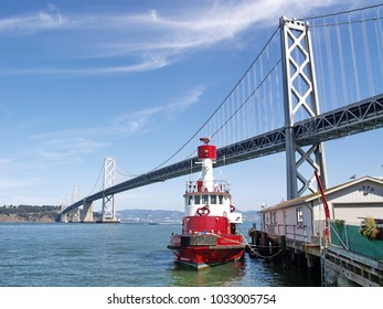 San Francisco Bay Bridge with a red ship