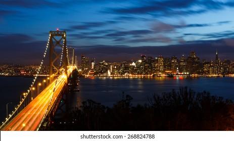 San Francisco Bay Bridge and skyline at night with city lights