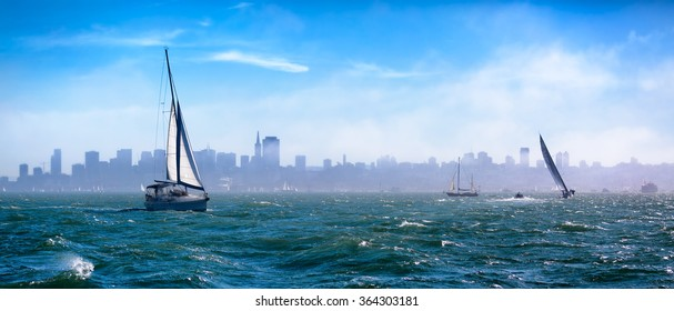 San Francisco Bay on a windy day with some fog and blue sky. Sailboats out in rough water. Skyline is visible through the fog. Image taken from the water with choppy waves in the foreground. Panorama