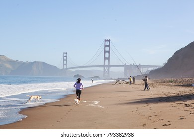 San Francisco, CA - 05 10 17: People running and fishing on baker beach close to Golden Gate bridge.