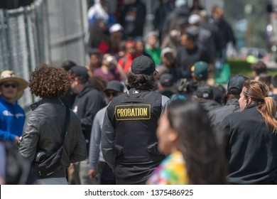 SAN FRANCISCO, CA - APR 20, 2019:  Crowds gather for the annual 420 celebration in Golden Gate Park.  A probation officer scans the crowd.
