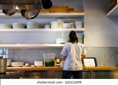 SAN FRANCISCO, CA- April 14, 2017: Restaurant kitchen worker in prep area seen from the back. Open shelving with stacks of dishes. Overhead pot rack.