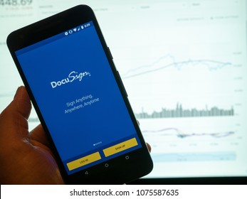SAN FRANCISCO, CA - APRIL 23, 2018: DocuSign mobile app held in front of a bright stock price chart on a computer monitor. The company is set for their IPO as a public company in April 2018.