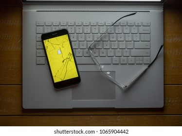 SAN FRANCISCO, CA - APRIL 8, 2018: Snapchat, disappear message social media app, logo on a broken cell phone sitting on a laptop next to glasses.