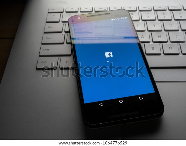 SAN FRANCISCO, CA - APRIL 8, 2018: Facebook app on phone sitting on laptop with Facebook desktop site reflecting on screen.