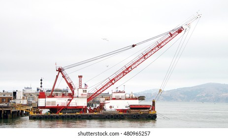 San Francisco, CA - August 20, 2016: Manson crane on a barge behind the Ferry Building in the San Francisco Bay. Manson works on construction and dredge projects in and around the San Francisco Bay.