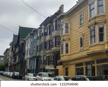 San Francisco, CA / August 5, 2018: Edwardian style architecture. Row of two story buildings in Nob Hill neighborhood in San Francisco. Cars parked on the street.