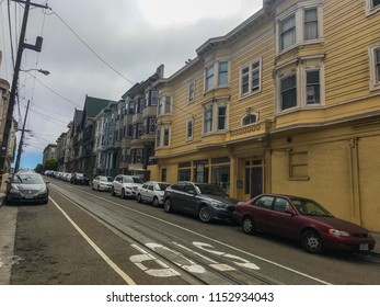 San Francisco, CA / August 5, 2018: Edwardian style architecture. Row of two story buildings in Nob Hill neighborhood in San Francisco. Cars parked on the street.Stop written on the lane.