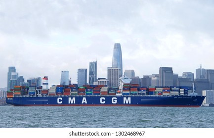 San Francisco, CA - February 02, 2019: Cargo Ship CMA CGM G WASHINGTON departing the Port of Oakland, City of San Francisco in the background