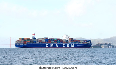 San Francisco, CA - February 02, 2019: Cargo Ship CMA CGM G WASHINGTON departing the Port of Oakland, heading towards Alcatraz and the Golden Gate Bridge.