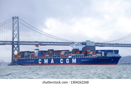 San Francisco, CA - February 02, 2019: Cargo Ship CMA CGM G WASHINGTON departing the Port of Oakland, passing under the Bay Bridge.