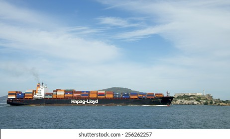 SAN FRANCISCO, CA - FEBRUARY 26, 2015: Hapag-Lloyd Cargo Ship KOBE EXPRESS passing Alcatraz Island in the San Francisco Bay Alcatraz. Alcatraz is a major historic tourist site and bird sanctuary.