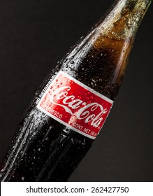San Francisco, CA - February 4, 2015:  Photo of a glass bottle of Coca Cola - Refreshing.  Wet with water ice droplets.