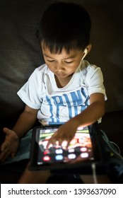 SAN FRANCISCO, CA - JULY 2: Young asian boy with headphones playing with a tablet computer. Tablet computers offer larger screens than phones and better portability than laptops.