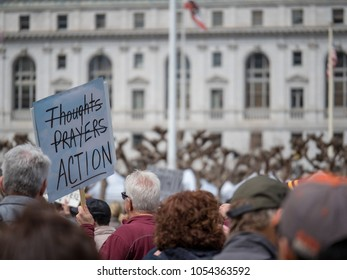 SAN FRANCISCO, CA - MARCH 24, 2018: Thoughts and prayers strike-through banner at March for Our Lives rally in San Francisco. The rally was sparked by the Stoneman Douglas school shooting.