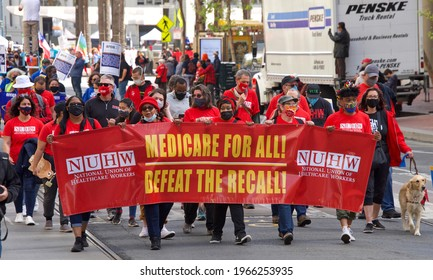 San Francisco, CA - May 1, 2021: Unidentified participants marching up Market Street celebrating May Day, also known as International Workers' Day.