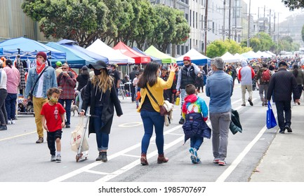 San Francisco, CA - May 29, 2021: Unidentified participants at Carnaval Festival in the Mission Distric, walking down the main street lined with venders selling their goods.