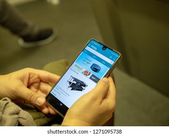 San Francisco, CA October 6, 2018: Woman shopping for Echo Dot on Amazon mobile app on iPhone screen while commuting on subway train