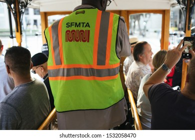 San Francisco, CA - October 6, 2019: SFMTA operator in vest controlling the famous cable trolley while tourists enjoy views and take photos on both sides.